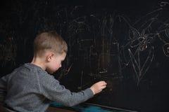 La vue arrière de l'étudiant masculin d'école primaire écrit sur le tableau noir Photo libre de droits