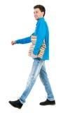 La vue arrière de l'homme bel allant porte une pile de livres Image libre de droits