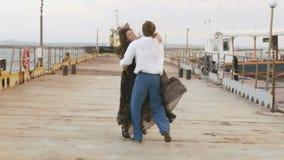 La vue arrière de l'homme courant après la femme Les couples étreignants sur le pilier clips vidéos