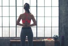 La vue arrière de la femme avec des mains étreintes derrière soutiennent dans la pose de yoga Images libres de droits
