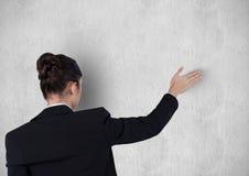 La vue arrière de la femme d'affaires avec le bras a augmenté contre le mur Photos stock
