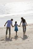La vue arrière de la fixation de famille remet la marche sur la plage Photographie stock libre de droits