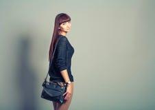 La vue arrière de la jeune femme occasionnelle dans le pantalon regardent en arrière Photographie stock libre de droits