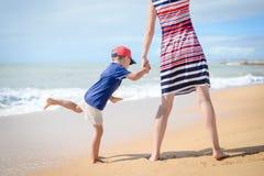 La vue arrière de la mère enthousiaste heureuse et l'enfant ont l'amusement sur la plage sur ensoleillé dehors Images stock