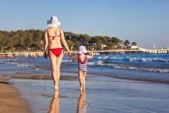 La vue arrière de la mère et la fille en mer échouent Photographie stock libre de droits