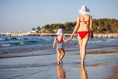 La vue arrière de la mère et la fille en mer échouent Photos stock