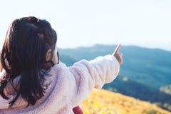 La vue arrière de la petite fille asiatique d'enfant a mis dessus le manteau soulèvent son bras photographie stock libre de droits
