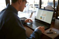 La vue arrière de plan rapproché de l'homme d'affaires caucasien remet la dactylographie sur le clavier d'ordinateur portable et  Images stock