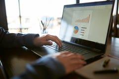La vue arrière de plan rapproché de l'homme d'affaires caucasien remet la dactylographie sur le clavier d'ordinateur portable et  Images libres de droits