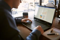 La vue arrière de plan rapproché de l'homme d'affaires caucasien remet la dactylographie sur le clavier d'ordinateur portable et  Photo stock