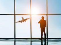 La vue arrière de silhouette du jeune homme d'affaires regarde hors d'une fenêtre panoramique et parle par le téléphone Images stock