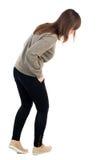 La vue arrière de tenir la jeune belle femme dans des jeans regarde vers le bas Image stock