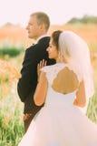 La vue arrière des épaules nues de la jeune mariée s'appuyant sur le marié dans le domaine de blé Photos stock
