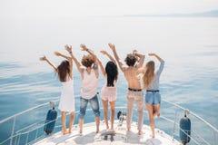 La vue arrière des amis célèbrent sur le voilier dans l'océan, bras augmentés Photographie stock