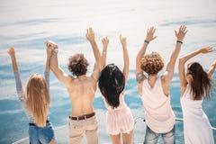 La vue arrière des amis célèbrent sur le voilier dans l'océan, bras augmentés Photo libre de droits