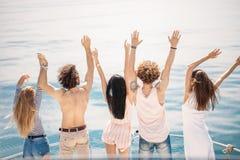 La vue arrière des amis célèbrent sur le voilier dans l'océan, bras augmentés Image libre de droits
