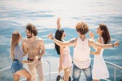 La vue arrière des amis célèbrent sur le voilier dans l'océan, bras augmentés Photographie stock libre de droits