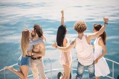 La vue arrière des amis célèbrent sur le voilier dans l'océan, bras augmentés Photo stock