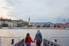 La vue arrière des couples attrayants dans l'amour tient des mains et apprécie le paysage de la rivière Danube à Budapest Photos libres de droits