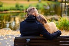 La vue arrière des couples se repose sur un banc Photo stock