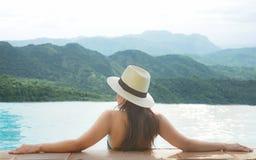 La vue arrière des femmes heureuses de mode de vie détendent et apprécient dans la piscine regardant le paysage de montagne Femme Images stock