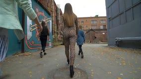 La vue arrière des filles dans des vêtements à la mode et à la mode marchant sur la rue de retour regardent Promenade d'amies Mar Images libres de droits