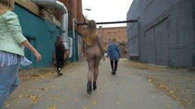 La vue arrière des filles dans des vêtements à la mode et à la mode marchant sur la rue de retour regardent Promenade d'amies Mar Photographie stock