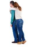 La vue arrière des jeunes embrassant des couples étreignent et regardent Image stock