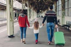 La vue arrière des mains amicales de prise de famille, portent la valise, allant avoir le voyage de voyage, posent sur la plate-f photos stock