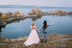 La vue arrière des nouveaux mariés élégants de couples avec des mains posent avant un lac sur la colline Cérémonie de mariage d'a images stock