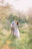 La vue arrière des nouveaux mariés de baiser dans la forêt ensoleillée la jeune mariée tient le bouquet Images libres de droits