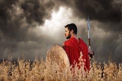 La vue arrière du guerrier portant dans le manteau rouge aiment spartiate Image stock