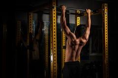 La vue arrière du jeune homme musculaire en bonne santé avec ses bras s'est étendue, torse sportif fort de modèle de forme physiq images libres de droits