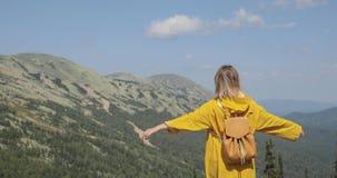 La vue arrière du randonneur féminin caucasien dans l'imperméable jaune se tient dans les montagnes banque de vidéos