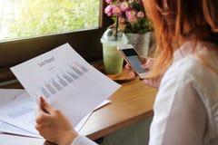 La vue arrière du téléphone portable avec la calculatrice APP est employée à la main de femme d'affaires dans son bureau Profonde images stock