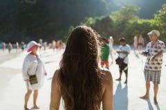 La vue arrière du voyageur féminin se tient sur la plage avec le groupe de touristes Photo stock