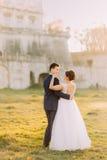 La vue arrière intégrale du marié étreignant la jeune mariée avec les épaules nues près du château démodé pendant Photo stock