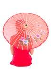 La vue arrière de la fille s'asseyante dans la robe rouge de Japonais avec le parapluie est Photos stock
