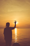 La vue arrière de silhouette de la femme détendent au bord de la mer et arrêt de représentation Photos stock