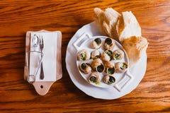 La vue ci-dessus de composition de nourriture a compris les coquilles et le pain d'escargot Il est entouré par des couverts Photo libre de droits