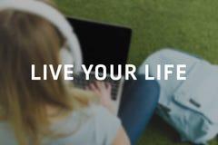 la vue courbe de la jeune femme se reposant sur l'herbe avec des écouteurs sur la tête et fonctionnant avec l'ordinateur portable photo libre de droits