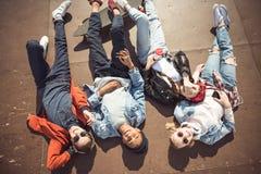 La vue courbe des adolescents groupent le mensonge ensemble et le repos Photographie stock