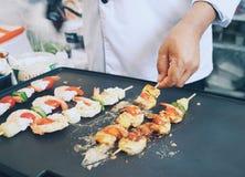La vue courbe du chef faisant cuire le BBQ frais de crevette sur chaud plat plat avec une participation de main Photos stock
