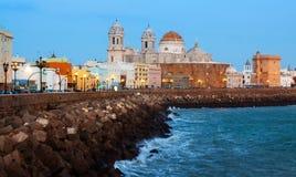 La vue crépusculaire de la cathédrale et l'océan marchent à Cadix Image stock