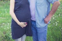 La vue cultivée de tir de l'attente parents étreindre et tenir des mains autour du ventre enceinte Grossesse, de maternité et nou Images stock