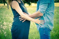 La vue cultivée de tir de l'attente parents étreindre et tenir le ventre Concept de la famille de grossesse, de maternité et nouv Images libres de droits