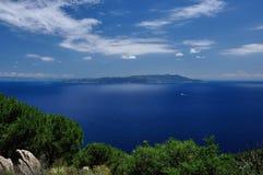 La vue d'île avec le bateau de forêt opacifie et ciel, Giglio, Toscane, Italie Image libre de droits