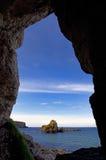 La vue d'île de Rocky Island et de moutons d'une caverne dans l'Antrim marchent Photographie stock libre de droits