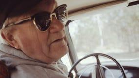La vue d'angle arrière du vieil homme envoie bonjour à l'appareil-photo et sort de la voiture banque de vidéos