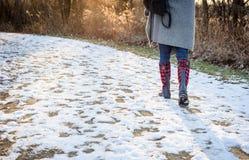 La vue d'angle faible de la femme marchant sur la neige a couvert la traînée en bois a photo stock